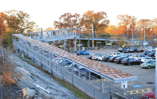 View of the current South Attleboro accessibility ramp prior to reconstruction. The ramp overlooks the semi-full parking lot on an autumn day during sunset.