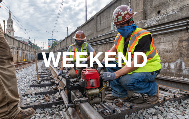 "Overlaid text reads ""Weekend."" A crew wearing face coverings, safety vests, and helmets works on rail."