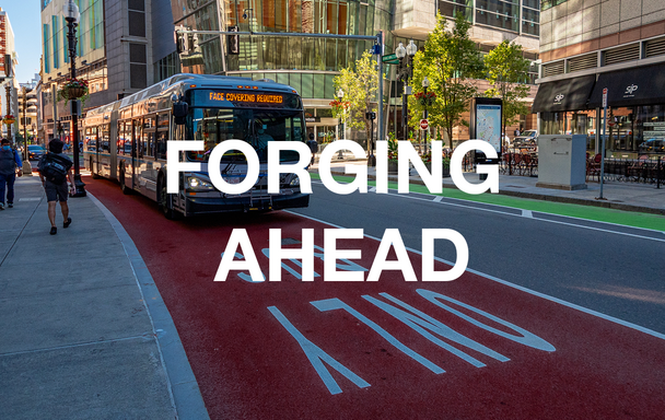 """Bus in a bus lane, with """"Face coverings required"""" in its headsign. Overlaid text reads """"Forging Ahead."""""""