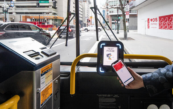 A rider taps their phone at one of the new CharlieCard reader prototypes installed on bus routes 28 and 39