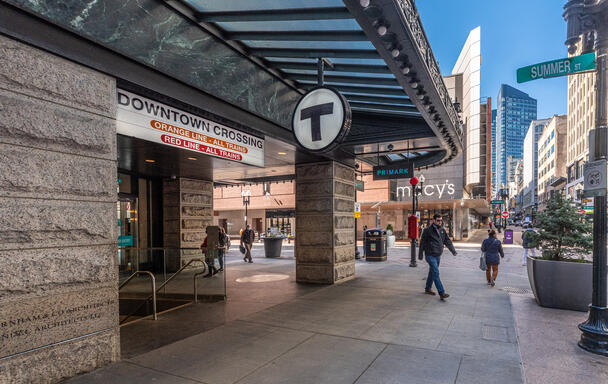 The Summer St entrance to Downtown Crossing station. Various pedestrians in face masks walk the street, and the Macys building is in the background