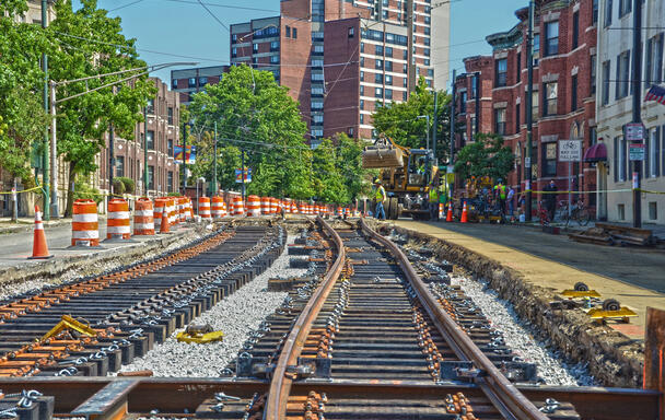 New track laid down for the Green Line E branch. There are a few construction workers in neon vests and hard hats in the background, next to a large piece of machinery