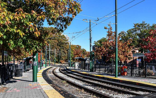 Green Line tracks at Washington Square station surrounded by foliage