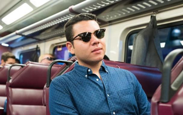 A young man in a blue shirt and sunglasses is seated on a Commuter Rail train.