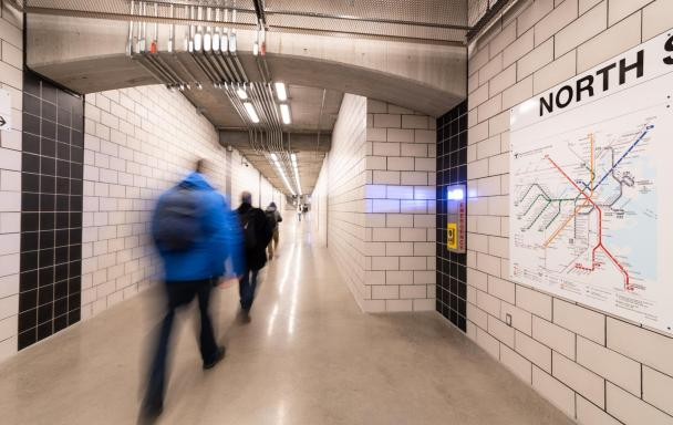 North Station underground walkway, with a system map of the T on the wall and riders walking