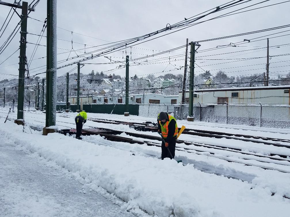 Two crewpeople in orange vests shovel tracks outside