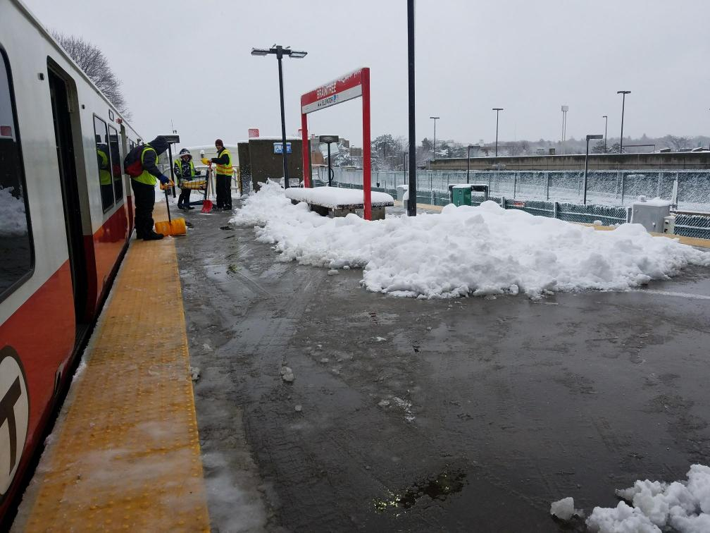 Outside on the Braintree platform, a Red Line train on the left, three members of a shoveling crew on the left as well. Piles of shoveled snow on the platform, to the right.