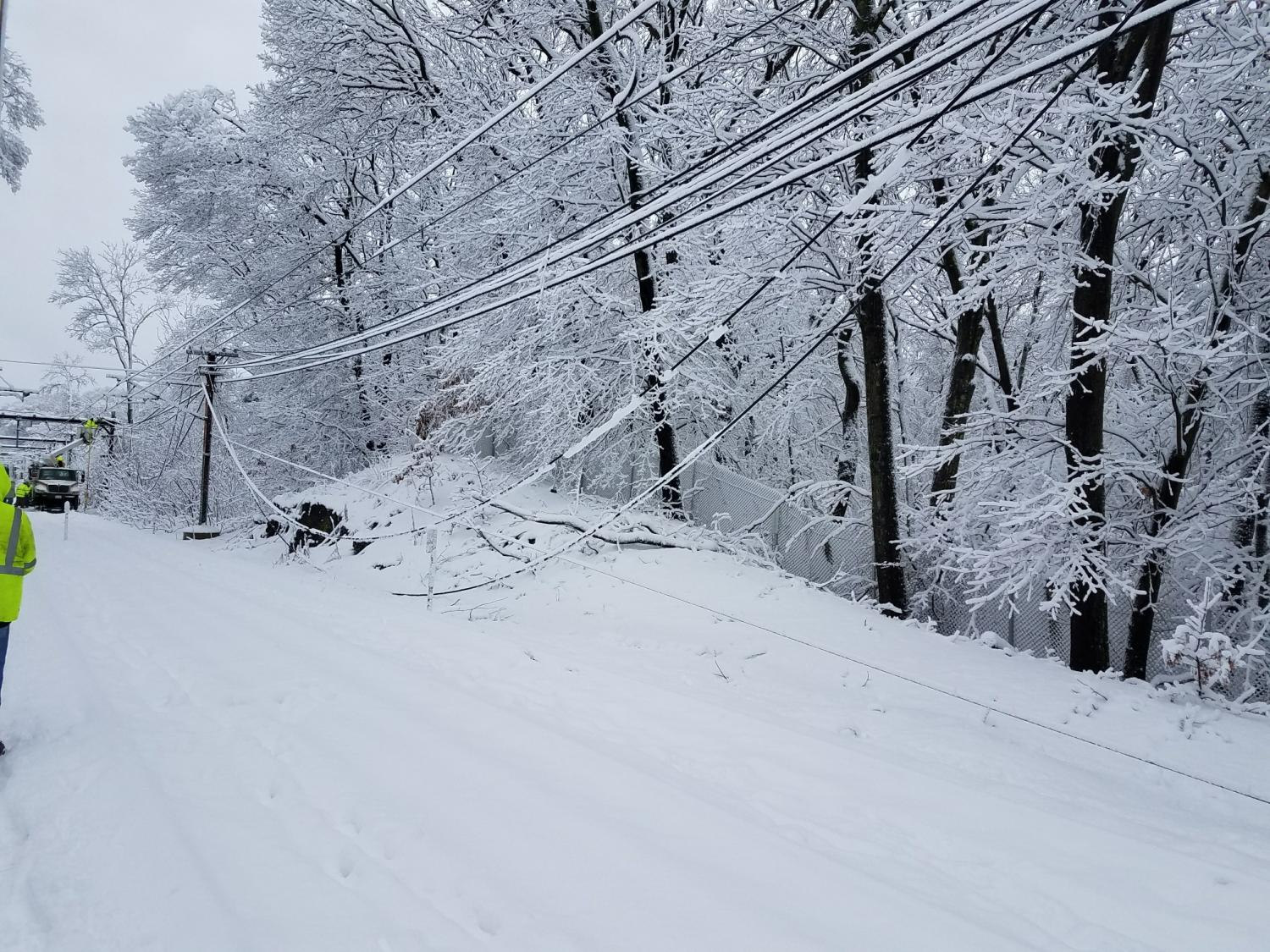 A wire droops down amid the snow as a crew on the left begins work