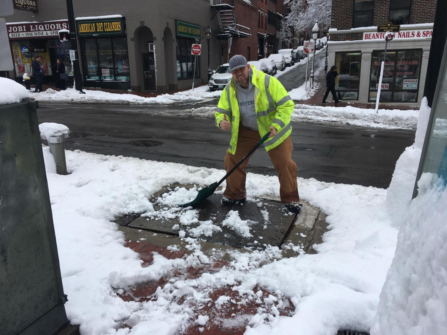 A crewman gives a thumbs up after he shoveled a hatch on the sidewalk near Bowdoin