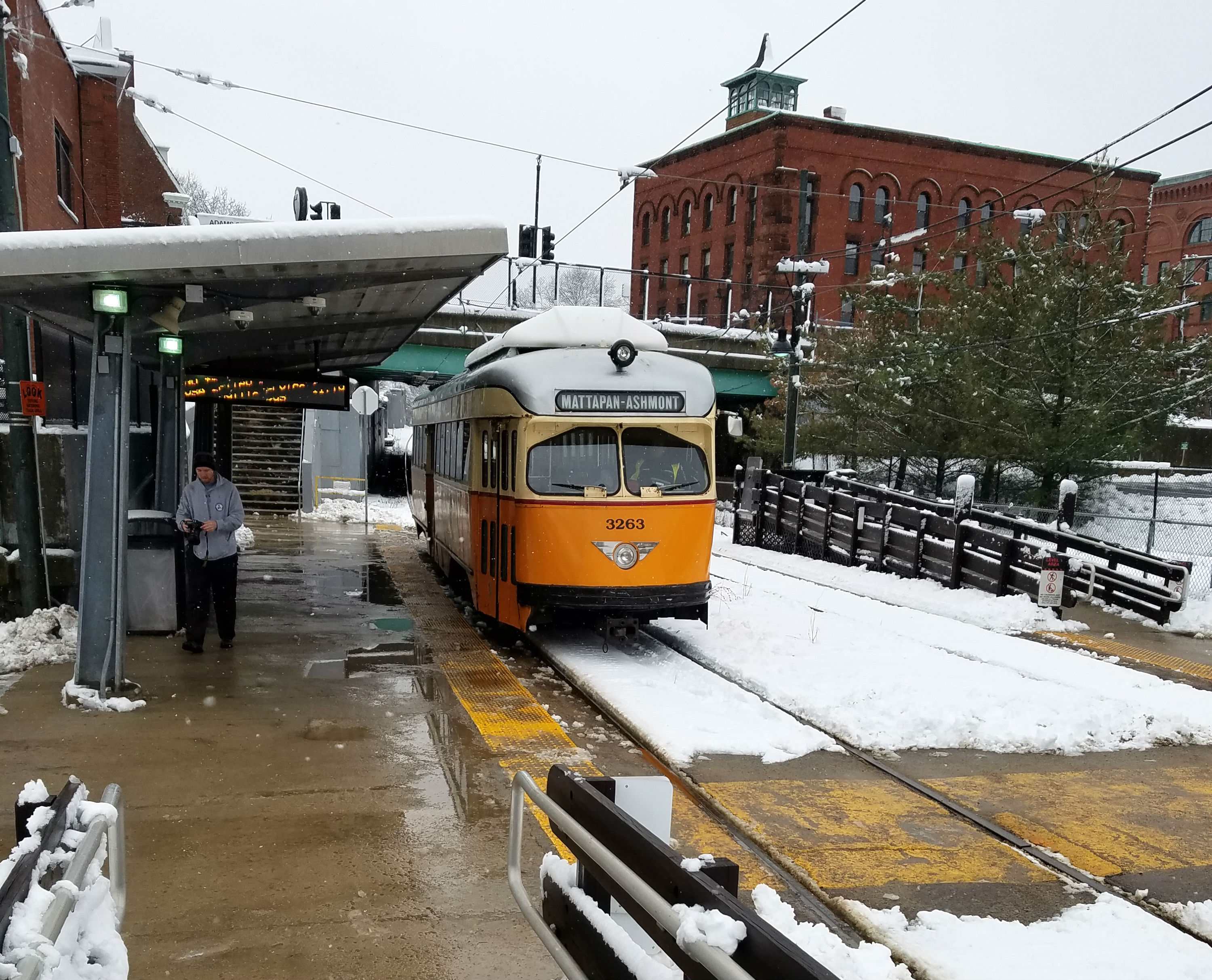 The Mattapan Trolley pulls out to the platform at Milton station. A rider who just disembarked walks off.
