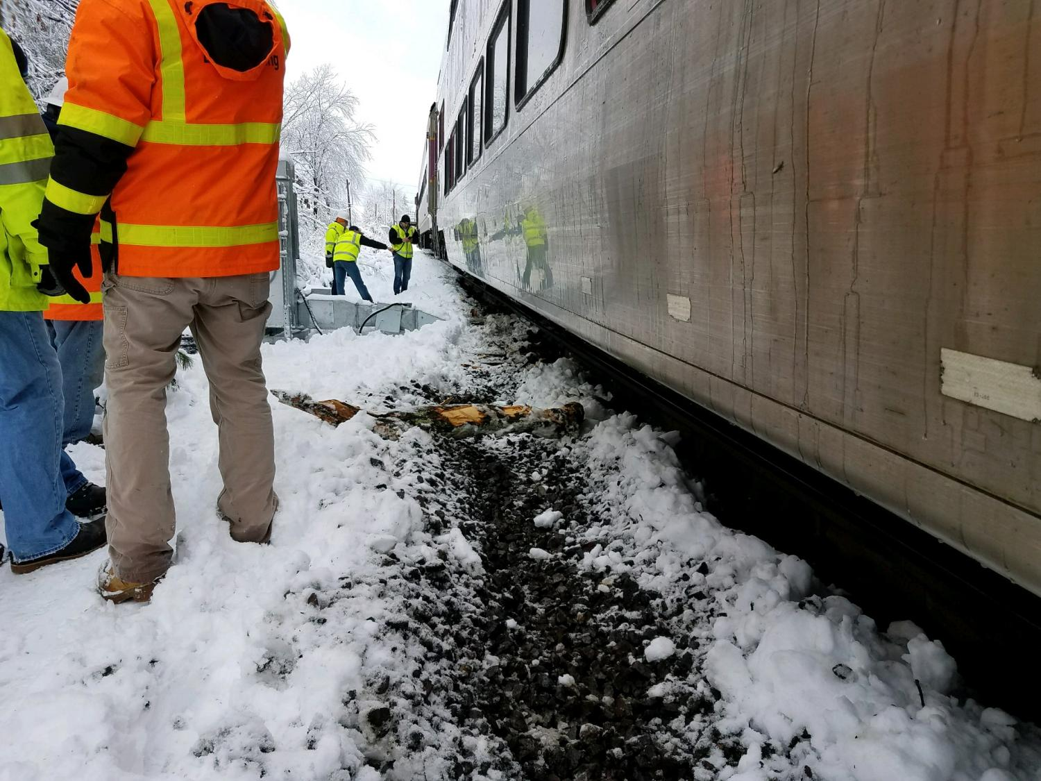 A commuter rail train on the right, with crewpeople on the left, attending to the derailment issues.