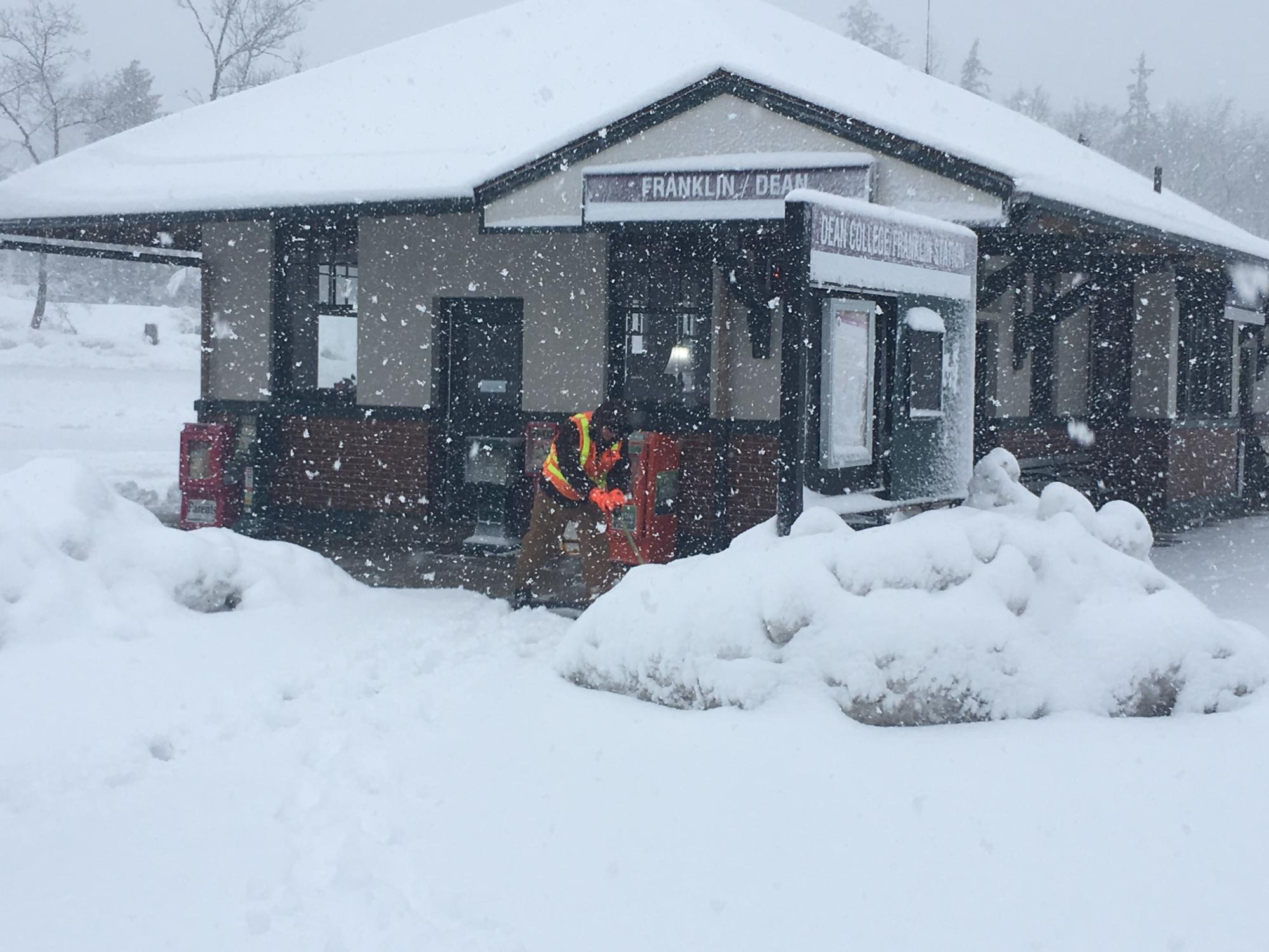 A crewman in an orange vest shovels snow outside the Franklin Commuter Rail stop