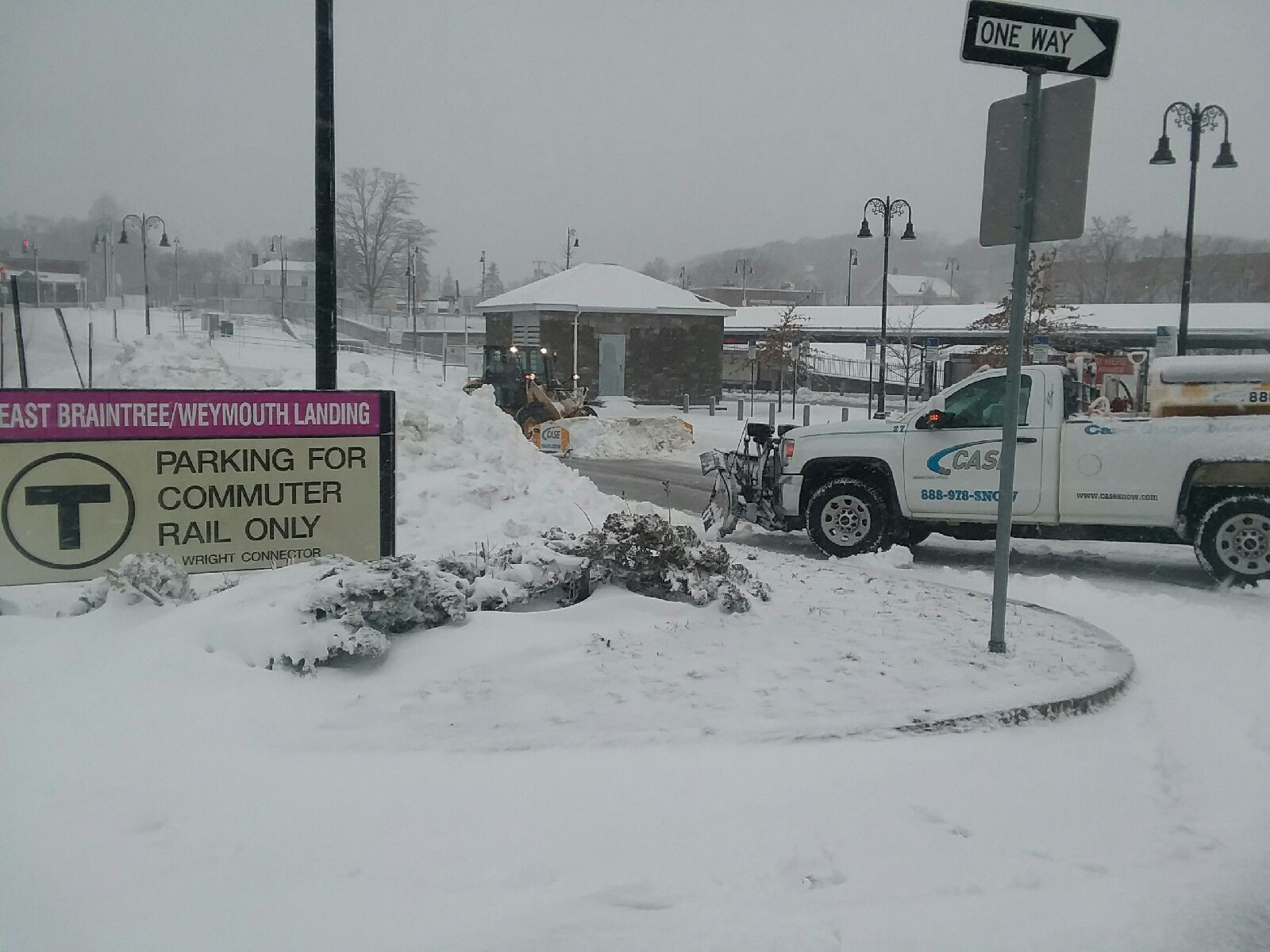 A truck with a plow attached pushes snow out of the entrance to the parking lot.